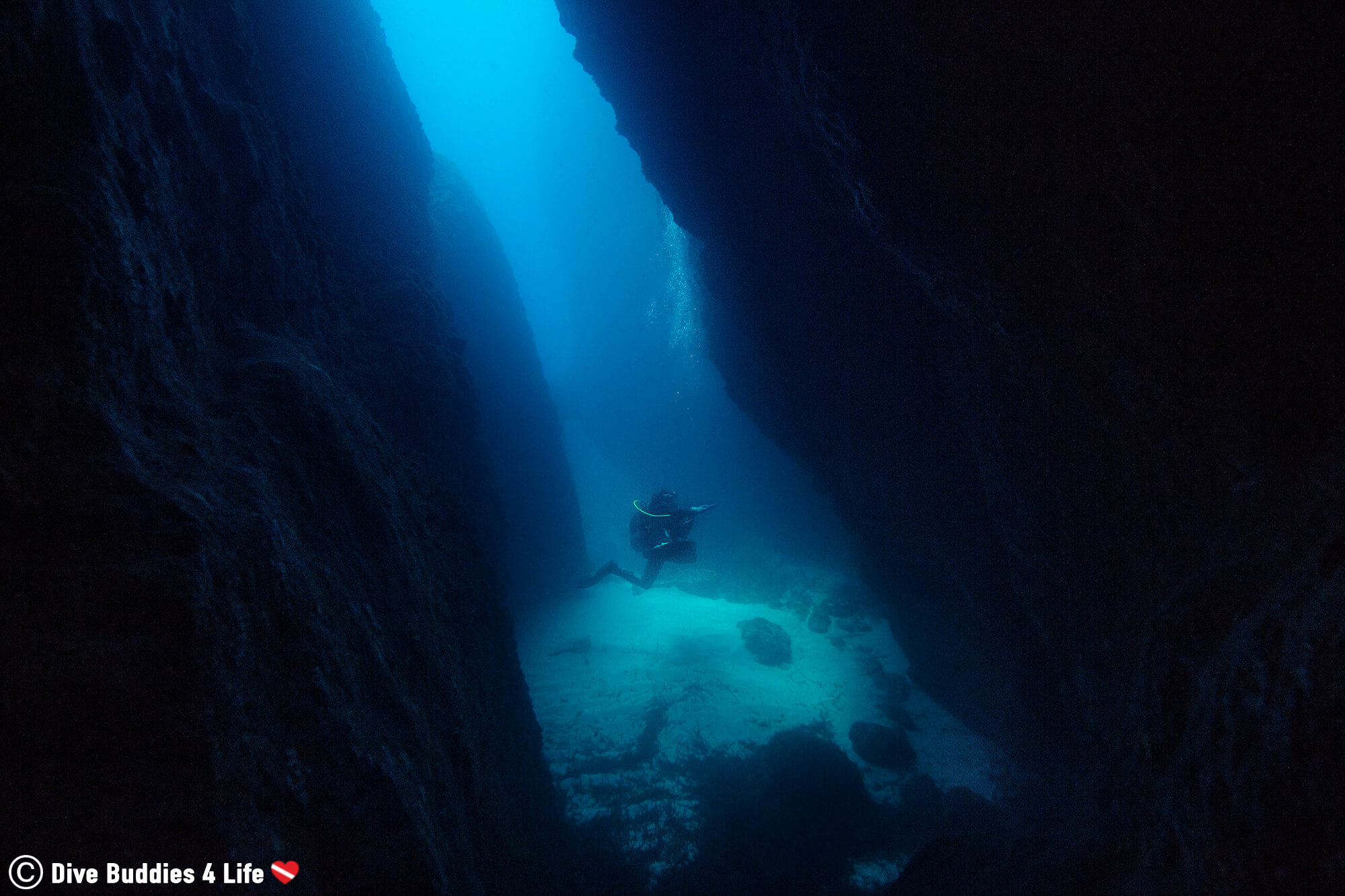 A Diver Scuba Diving Between Two Rock Walls Into A Cave On Zakynthos Island, Greece