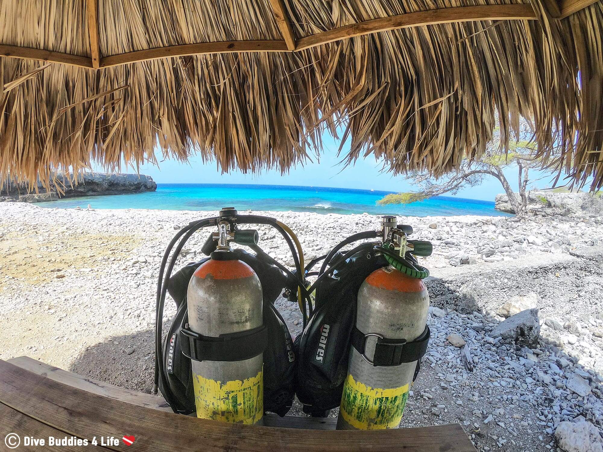 A Paire Of Scuba Diving Tanks At A Table Close To The Ocean In Bonaire, Caribbean