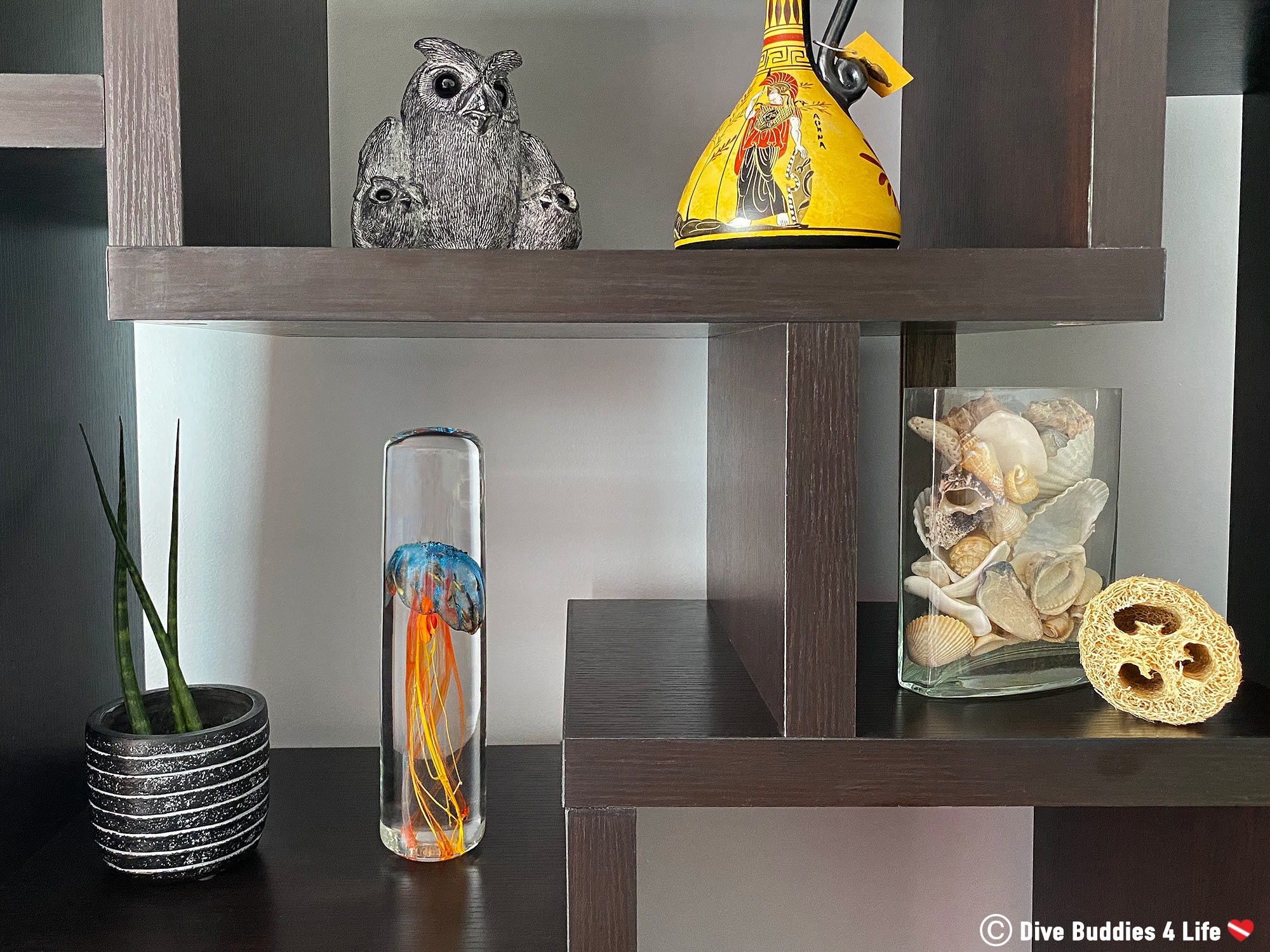 A Shelf With Home Decor Displaying The Glass Jellyfish Statue