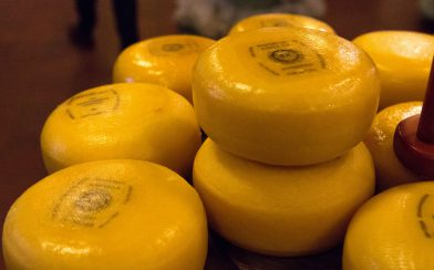 A Stack Of Yellow Cheese Wheels In Gouda