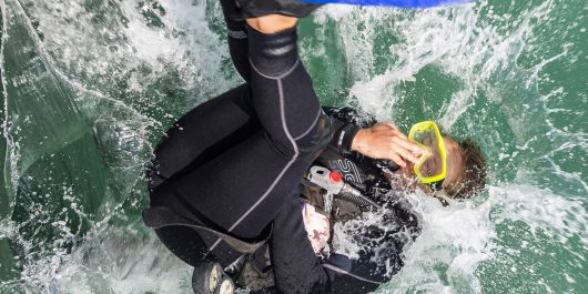 A Woman Diver With A Yellow Scuba Mask Rolling Into The Water With Scuba Diving Gear In Mexico