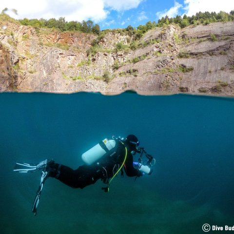 Ali Diving At The Surface Of The Water In Dayhouse (Chepstow) Quarry, Wales, UK