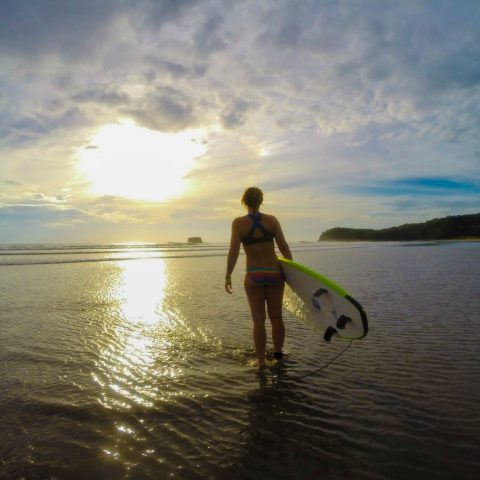 Ali Holding her Board in the Sunset