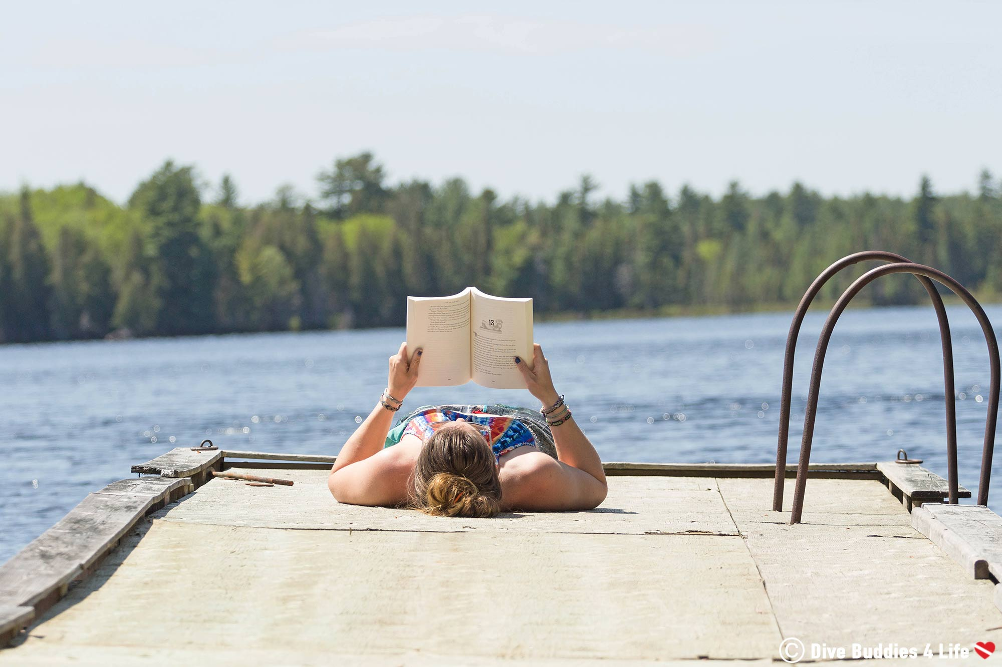 Ali Laying On A Dock Reading Deep Roots Dive Novel By The Water