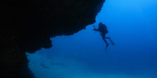 Ali Scuba Diving Silhouette Coming Out Of A Cave On Lanzarote, Canary Island, Spain