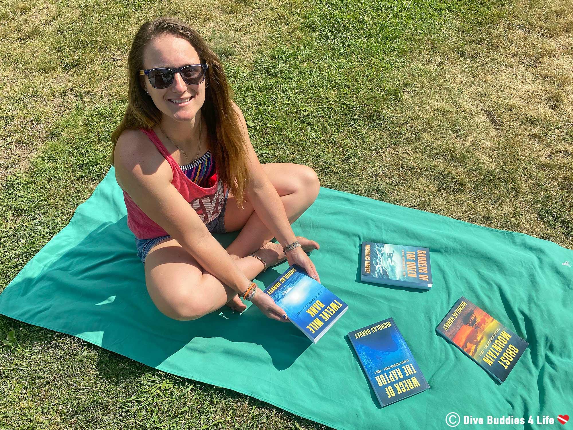 Ali On A Beach Towel With A Collection Of Nicholas Harvey's AJ Bailey Scuba Diving Novels