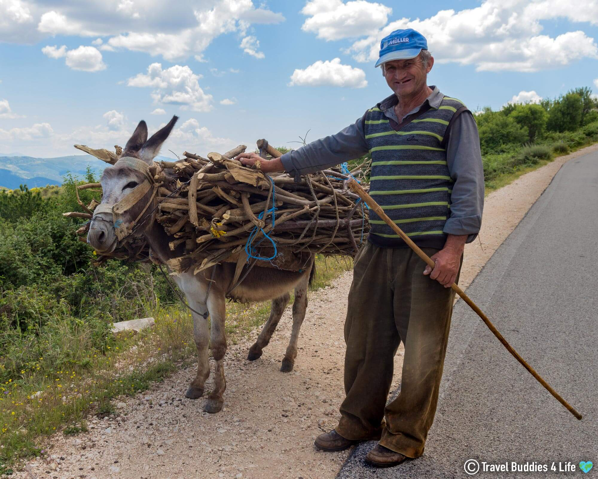 An Albanian Man And His Donkey Walking Along The Side Of The Road, In Albania, East Europe