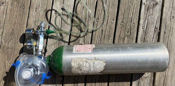An Scuba Oxygen Administration Bottle Laying On A Deck Ready To Use For First Aid On A Scuba Injury