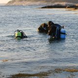 A Trio of Divers Gearing Up in their Scuba Stuff