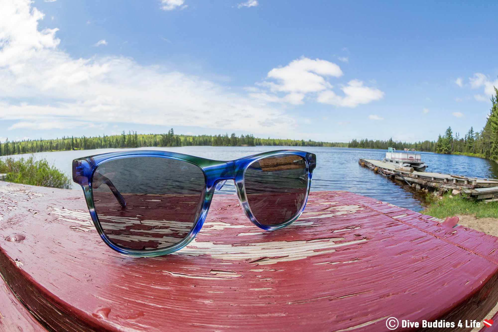 Fisheye Look At The Wildwood Sunglasses On A Picnic Table Beside The Water