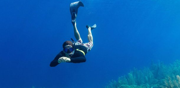 Joey Diving Down Underwater With His Snorkeling Equipment In Bonaire, Dutch Caribbean