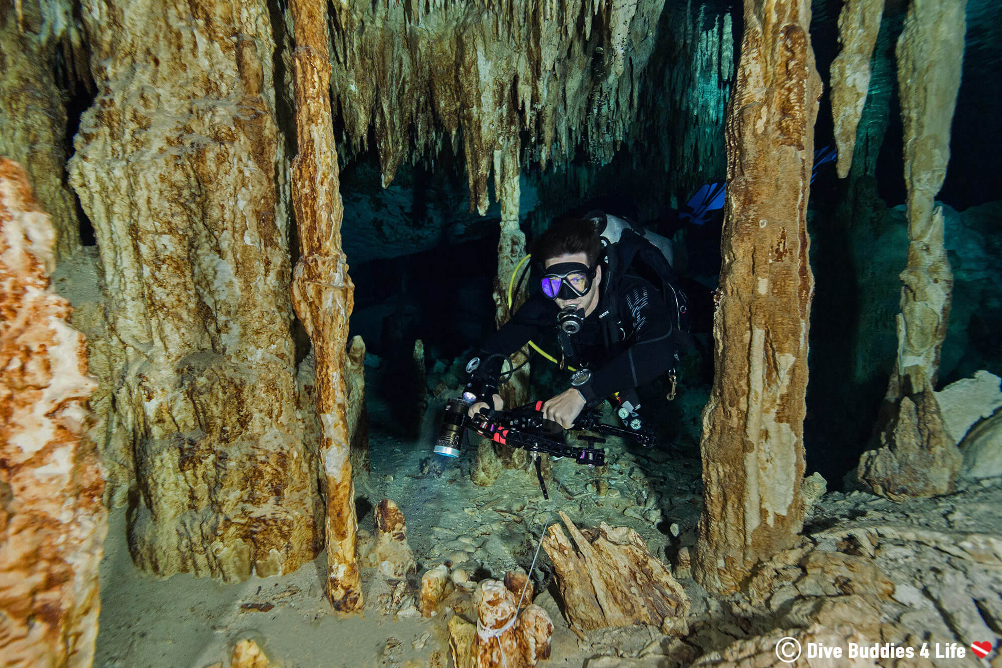 Joey Scuba Diving Through Some Pillars Of Stalagmites And Stalactites In Tulum, Mexico