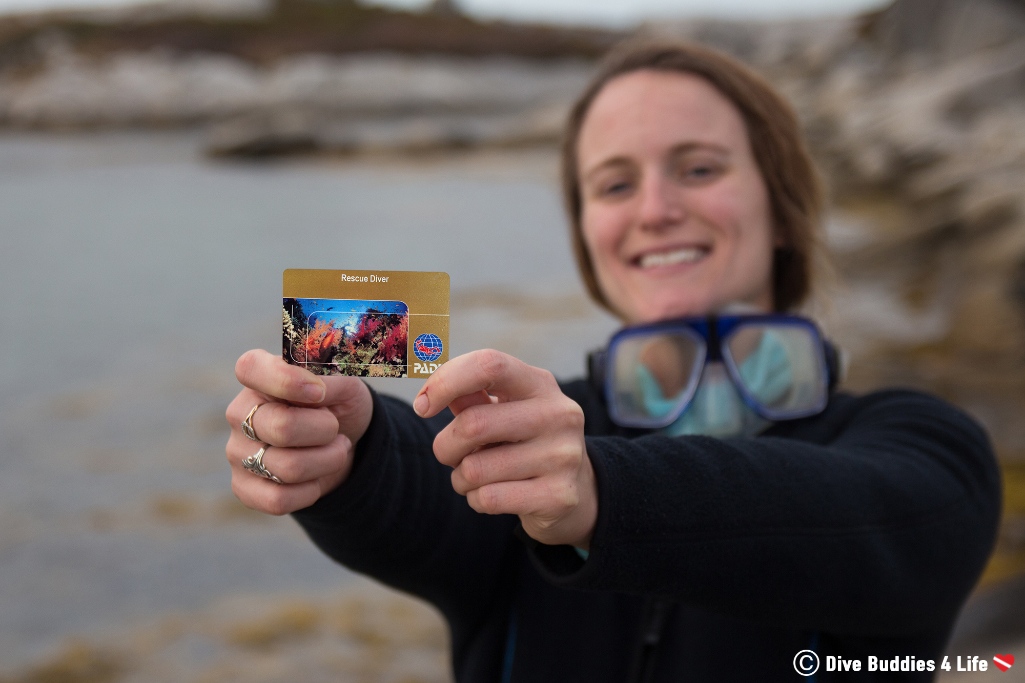 Scuba Diver Ali Holding Her PADI Diver Certification Beside The Ocean In Canada