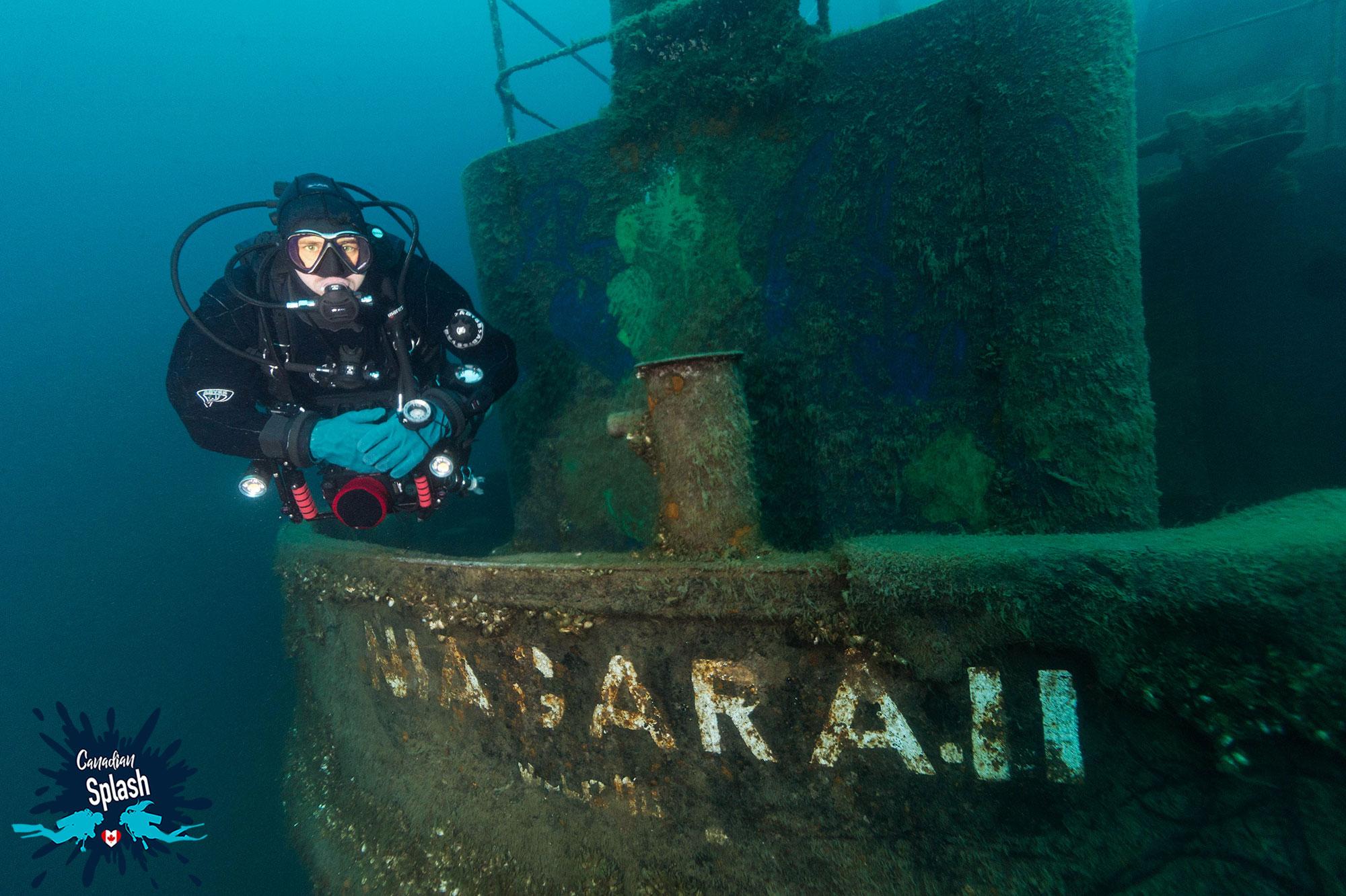 Scuba Diver Joey Swimming Beside The Back Of The Niagara II Shipwreck In Tobermory, Ontario