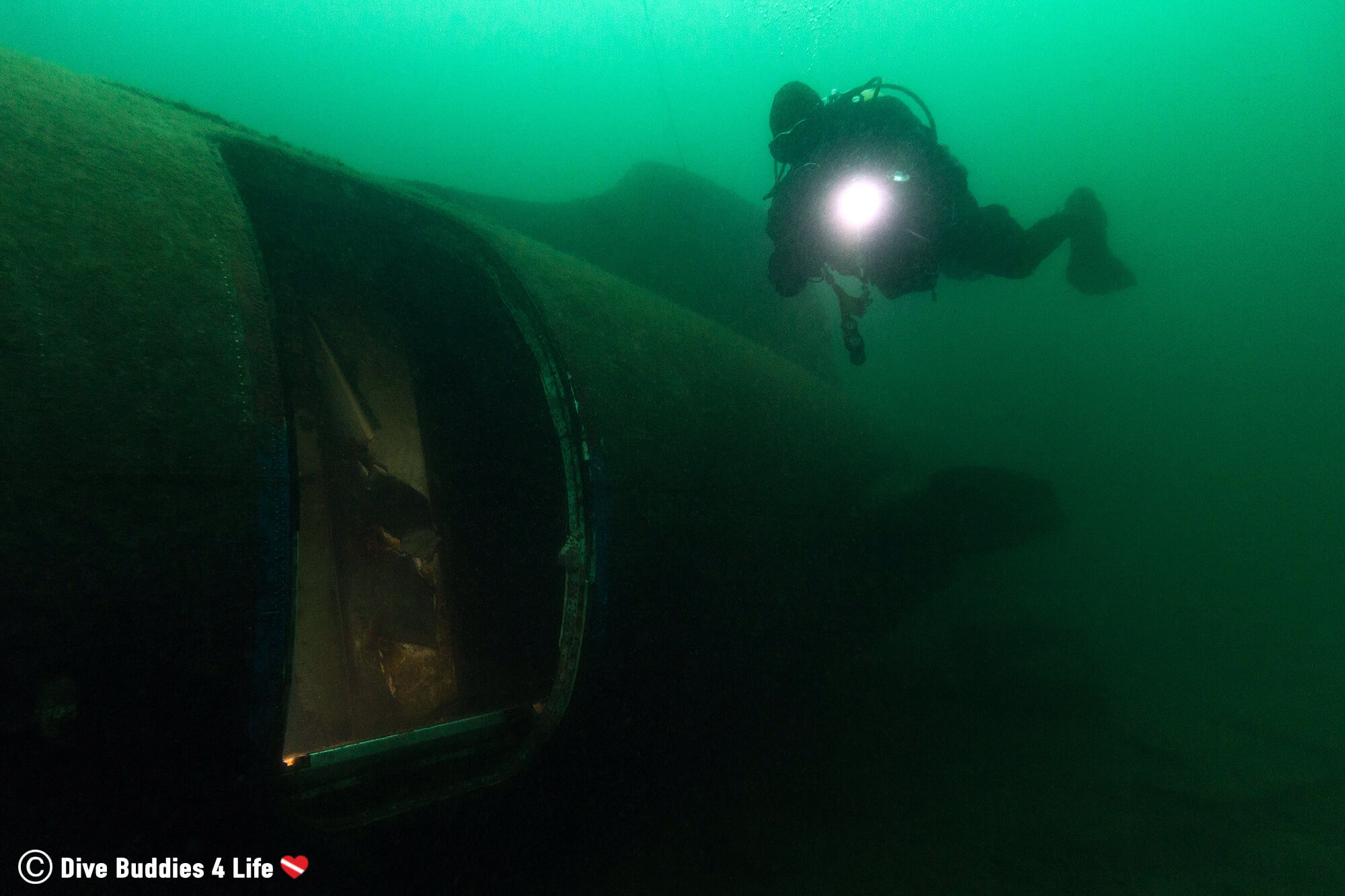 Scuba Diver In Vobster Quay With The Tail Of An Airplane And A Dive Torch, England, United Kingdom