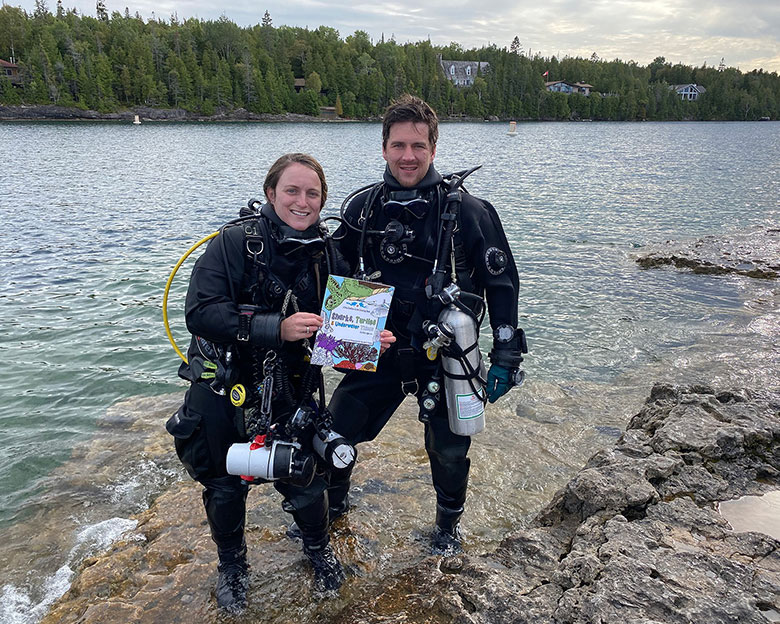 Scuba Divers Joey And Ali Holding Their New Educational Colouring Book At The Water