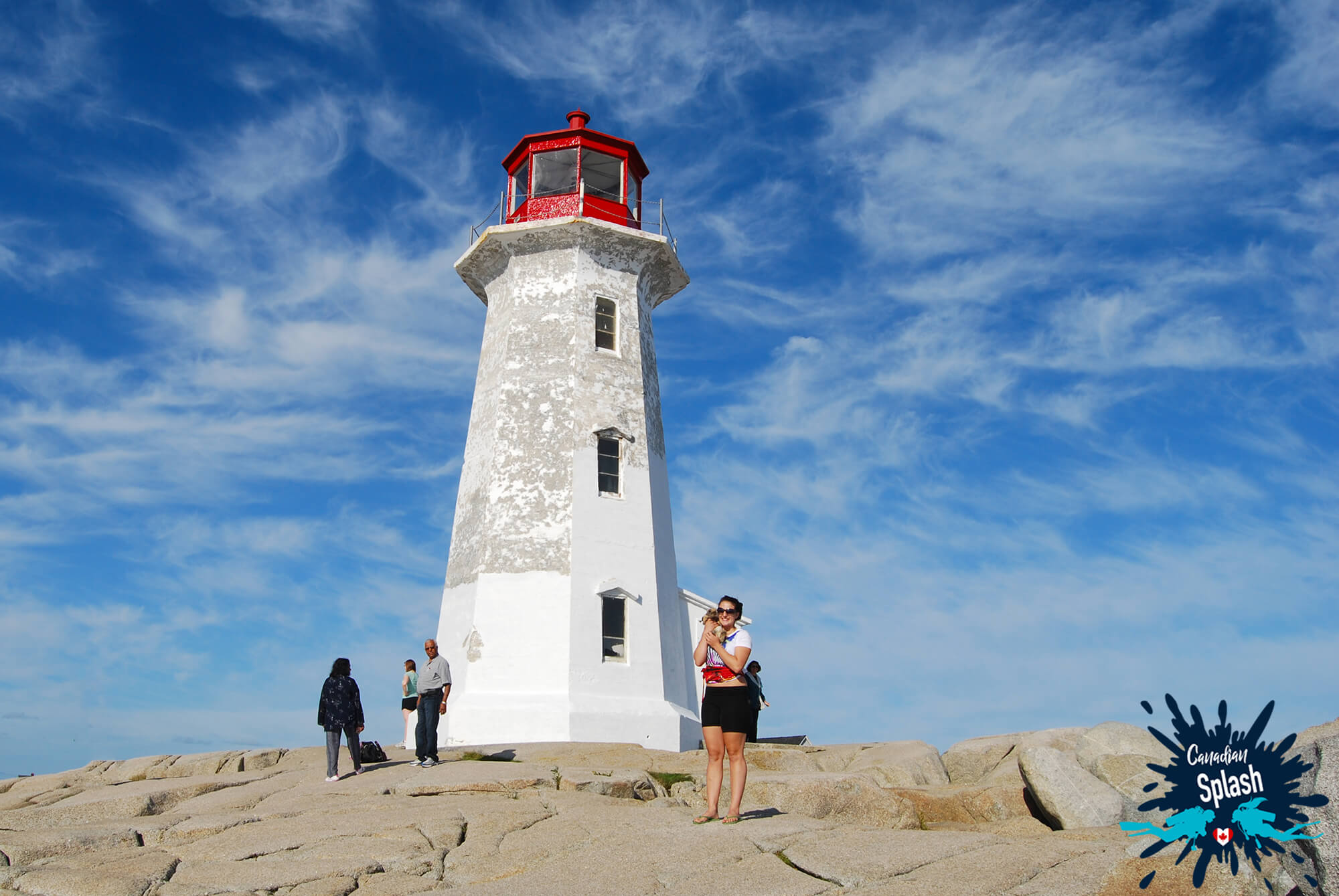 Standing At The Foot Of The Peggy's Cove Iconic Lighthouse In Nova Scotia, Canadian Splash