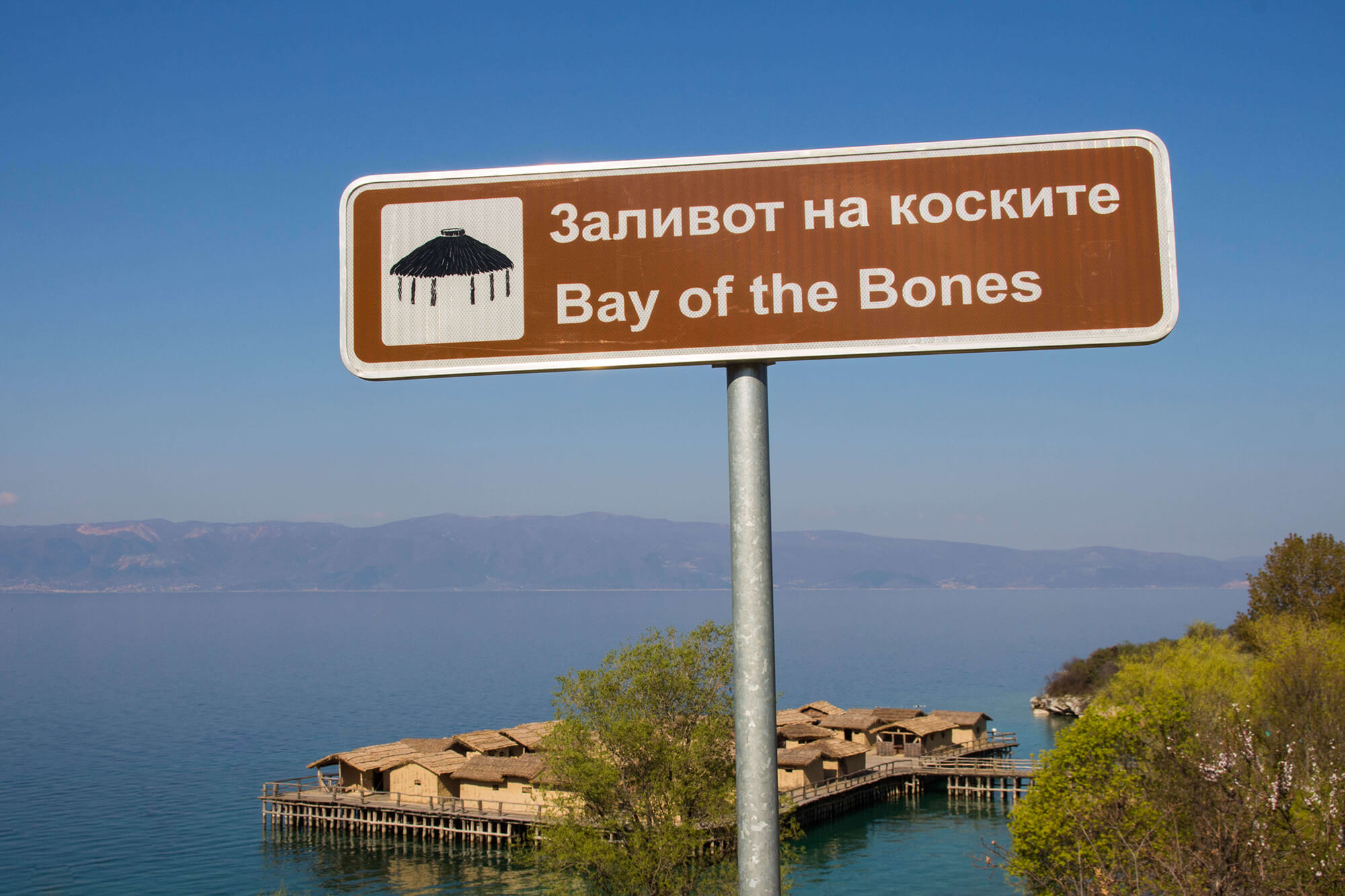 The Bay Of Bones Sign With The Houses and Lake In Behind