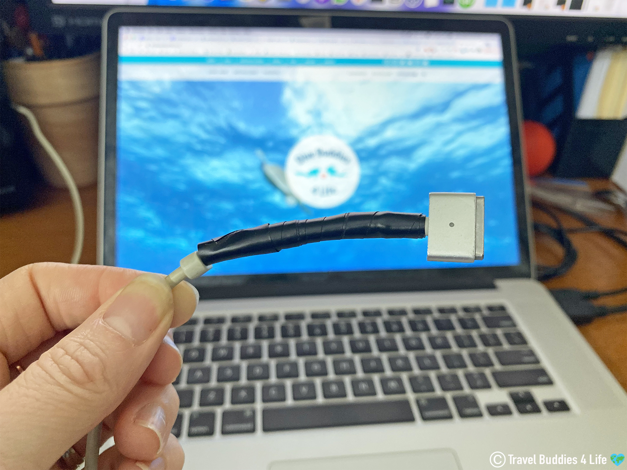 The Broken Charging Cable Of A Computer Fixed With Electrical Tape