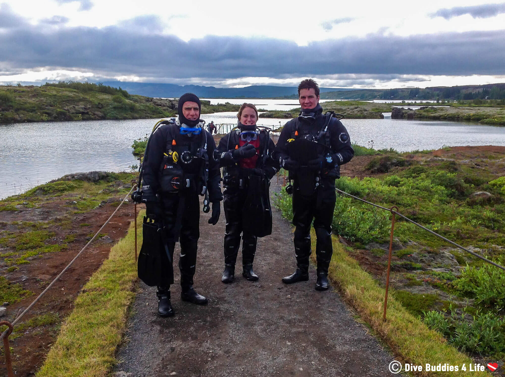 Three Scuba Divers Looking Frozen After Emerging From A Dive In The Silfra