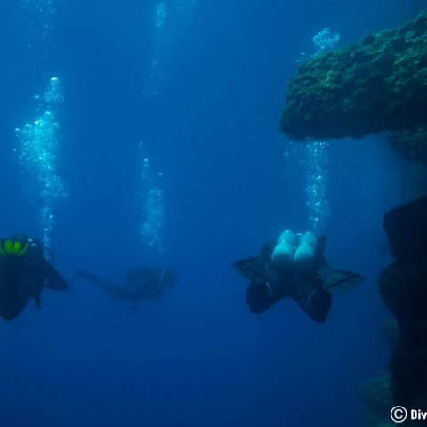 Three Scuba Divers Swimming At A Deep Scuba Diving Site In Dubrovnik, Croatia
