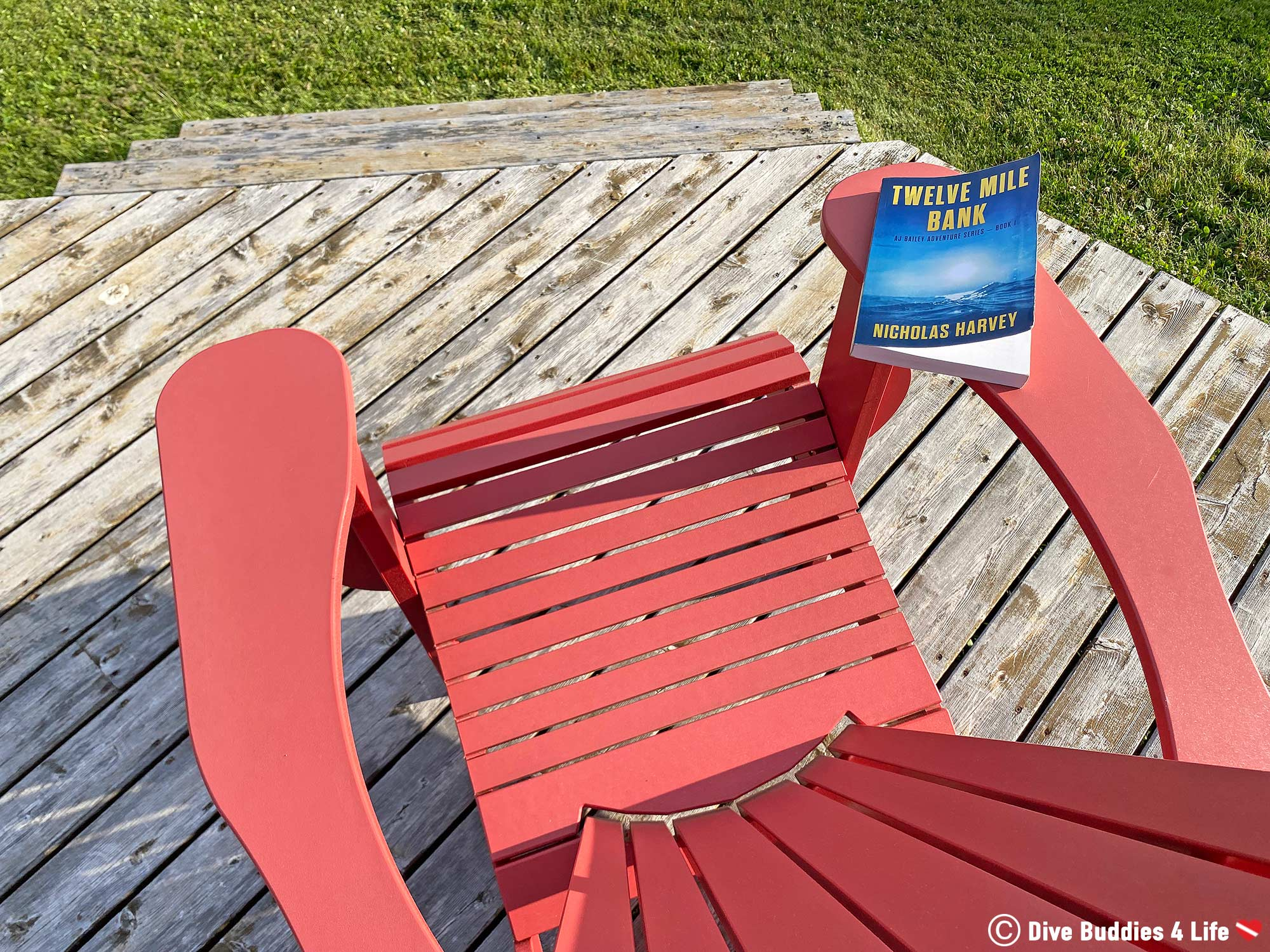 Twelve Mile Bank Scuba Diving Book Laying On The Edge Of A Red Muskoka Chair