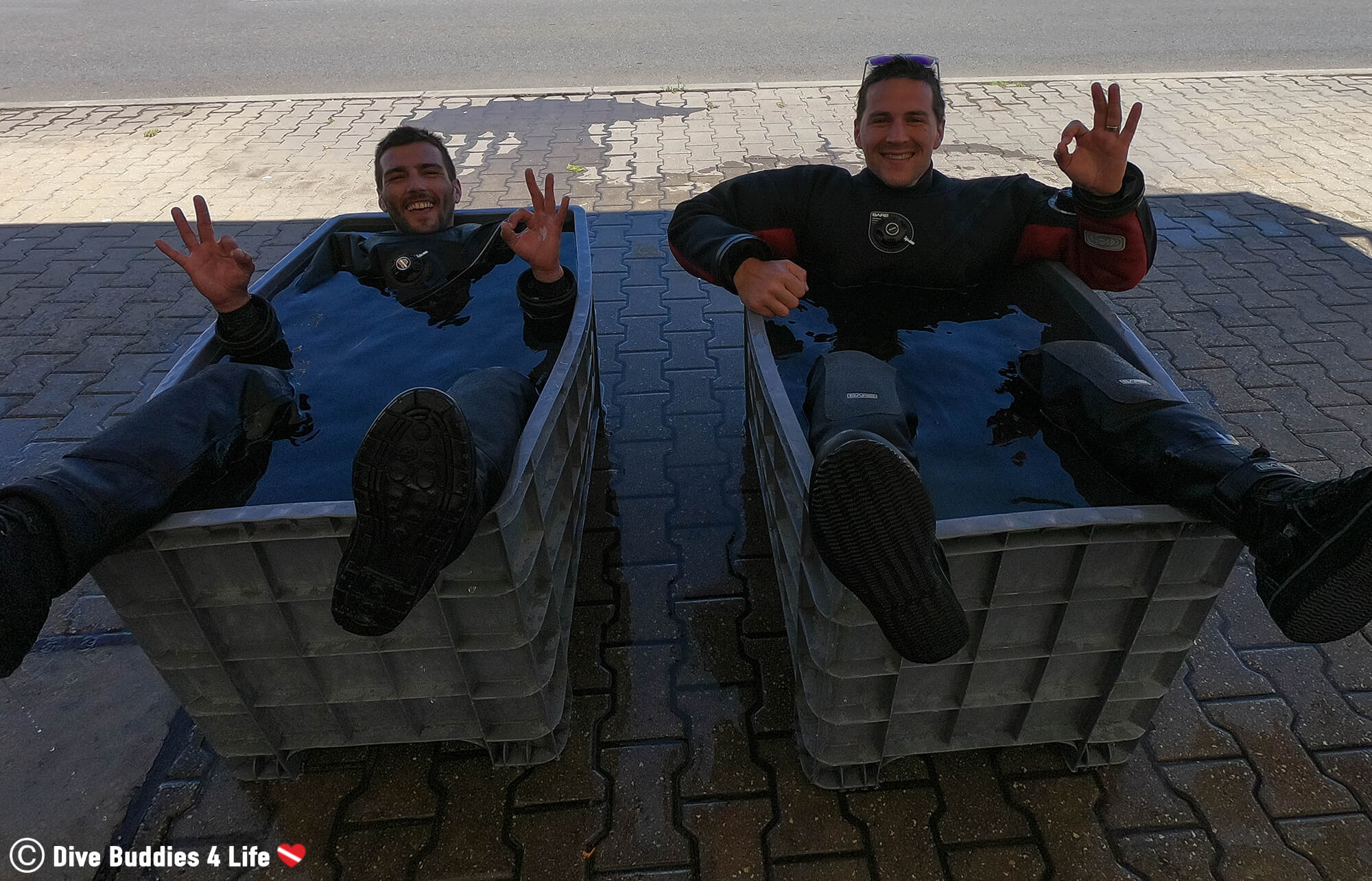 Two Divers Sitting In A Rinse Bin Cleaning Off Their Dive Equipment After A Scuba Dive In Sesimbra, Portugal, Europe