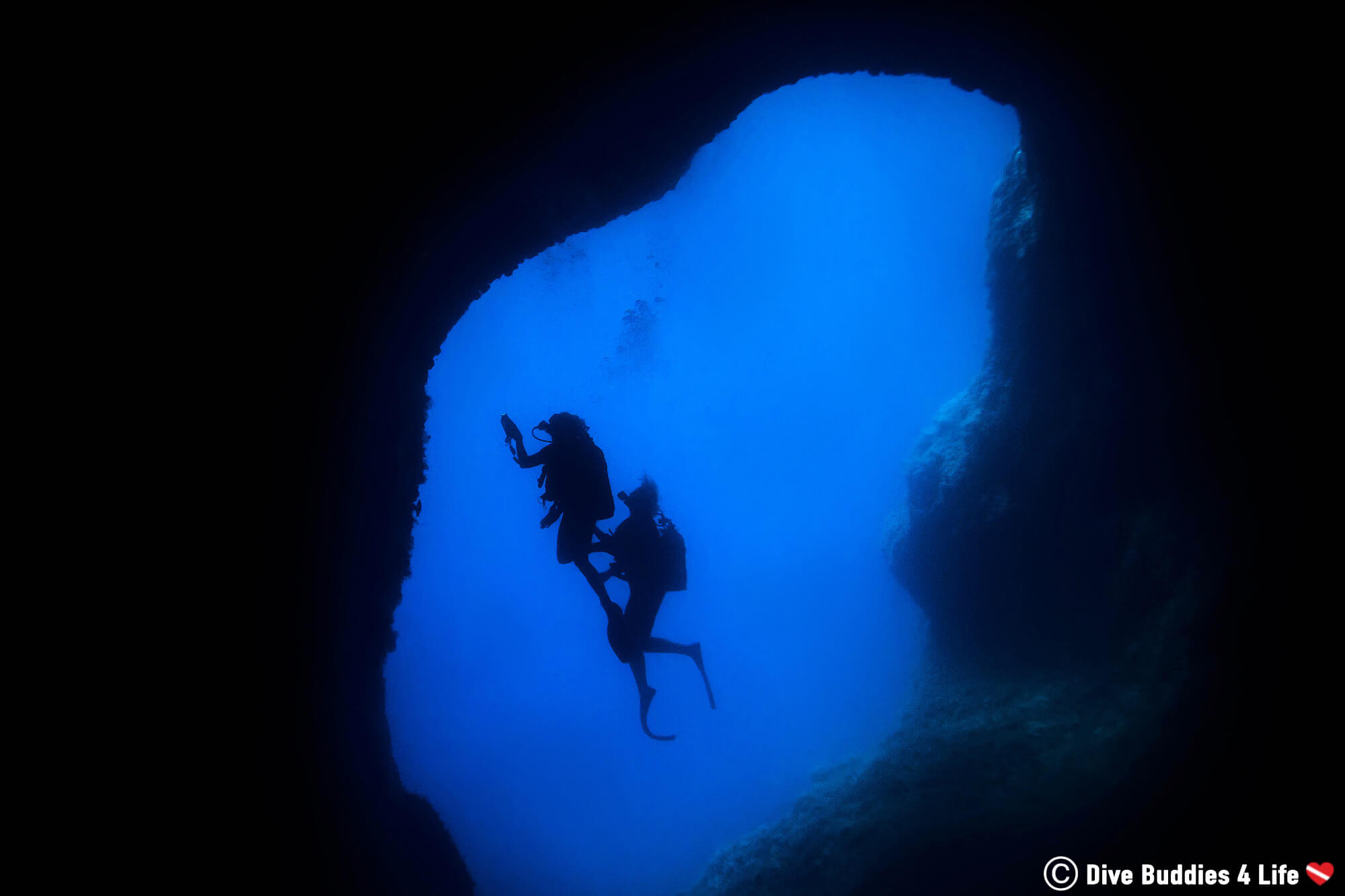 Two Scuba Divers In The Blue Waters Of The Mediterranean Sea, Amalfi, Italy